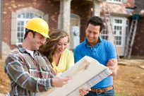 Contractor in a yellow hardhat reviews plans with a smiling couple in front of their house
